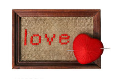 Embroidered word love. In the frame with knit ball in a form of a heart pierced with needle isolated on white background with clipping path Stock Image