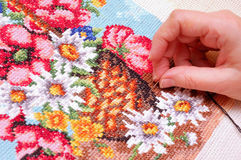 Embroidering a picture. Woman embroidering a picture of flowers (cross stitch Stock Photo