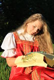 Embroidery. Russian girl in the national sarafan embroiders on the nature Stock Image