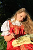 Embroidery. Russian girl in the national sarafan embroiders on the nature Stock Photography
