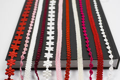 Embroidery. A detail of several red, pink and white embroidery - laces on textile book cover background - sewing supplies Royalty Free Stock Photos