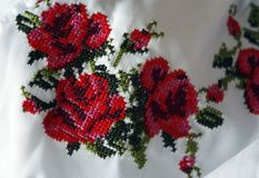 Embroidery with beautiful colorful red roses and green leaves, closeup. Cross-stitch texture, folk costume royalty free stock photos