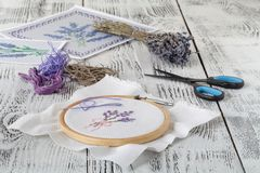 Embroidery bouquet of lavender and tools of needlework Stock Photos