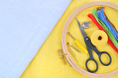 Embroidery and cross stitch accessories. Embroidery and cross stitch accessories on yellow and light blue linen fabric. Embroidery hoop, scissors, thread Royalty Free Stock Photos