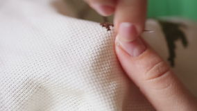 Embroidery cross stitching. Woman hands doing cross-stitch. A close up of embroidery stock footage