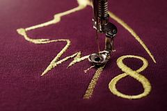 Embroidery with embroidery machine of dog silhouette and number 2018  in gold on claret fabric - chinese new year concept. Close up view on process of atin Royalty Free Stock Photography