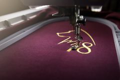 Embroidery with embroidery machine of dog silhouette and number 2018  in gold on claret fabric. Chinese new year concept in bright luxury light mood Royalty Free Stock Photo