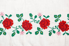 Embroidery flowers. Embroidery red flowers on the linen textile Royalty Free Stock Photography