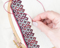 Embroidery fragment. Yarn, fabric. Fragment of embroidery on linen and hands of the master Royalty Free Stock Images
