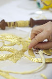 Embroidery in gold. The first plane of a woman realizing embroidery in gold Stock Photo