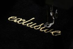 Embroidery of gold lettering & x22;exclusive& x22; on black velvety fabric with embroidery machine. Diagonal top view from right Royalty Free Stock Photos