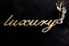 Embroidery of gold lettering & x22;luxury& x22; on black velvety fabric. With embroidery machine - top view final stitch Stock Photo