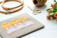 Embroidery, hoop, scissors, flowers on white wooden background royalty free stock photography