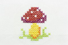 Embroidery of the image of a mushroom. Manual embroidery a dagger of the image of a mushroom Royalty Free Stock Photo
