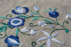 Embroidery on linen. Flower-shape embroidery on a gray linen Royalty Free Stock Image