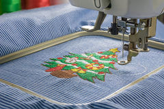 Embroidery machine in close up shot. Picture of embroidery machine in close up shot and complete christmas tree design on fabric Stock Images