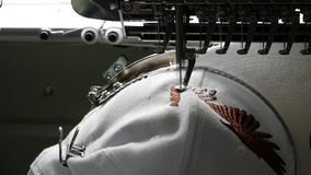 The embroidery machine creates an emblem on the cap`s surface. Industrial machines stock video