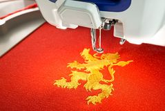 Embroidery machine and  gold lion design on red cotton fabric shirt, close up picture Stock Photography