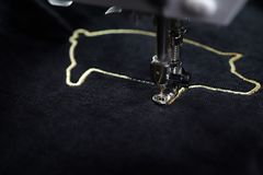 Embroidery machine stitching 2019 chinese new year motive with precious gold yarn on black velvetely fabric in dark surrounding. Embroidery machine stitching royalty free stock images