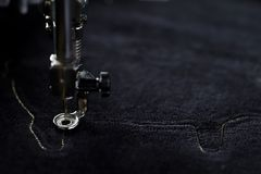 embroidery machine stitching outline of a pig on black velvetely fabric in dark light mood royalty free stock photos