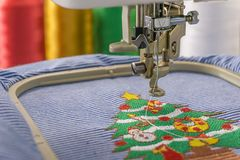 Embroidery machines and Christmas. Tree design on fabric 3 color threads close up shot Stock Images