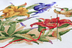 Embroidery Needle and Thread with Cross Stitch in Background Royalty Free Stock Photography