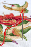 Embroidery Needle and Thread with Cross Stitch in Background Royalty Free Stock Image