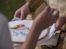 embroidery O processo de bordar um anjo com uma cruz imagens de stock