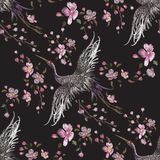 Embroidery oriental seamless pattern with cranes and cherry blossom. Stock Photos