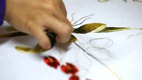 Embroidery of a picture with silk threads. The process of creating a close-up stock video footage