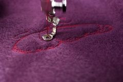 embroidery of pink butterfly on purple boiled wool - first wing in progress - moving needle bar royalty free stock images