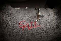 embroidery of red lettering SALE on soft grey fabric with embroidery machine - top view with moving needle bar Royalty Free Stock Photo