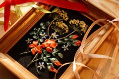 Embroidery ribbons on a black background. Handmade. Embroidered bright colors on a black background. The picture in the frame. Made by hand Stock Photo