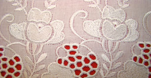 Embroidery rishelye on a white batic. On a red background royalty free stock photography