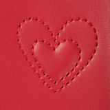 Embroidery in shape of two heartssmall and big on pink leather Stock Photos