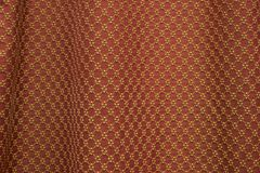 Embroidery textile pattern. Repeatable yellow threads embroidery pattern on red textile Royalty Free Stock Photography