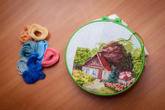 Embroidery work on the table. Interesting hand embroidery from home in work with a needle and green thread Stock Image
