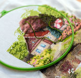 Embroidery work on the table. Interesting hand embroidery from home in work with a needle and green thread Royalty Free Stock Images