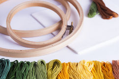Embroidery yarns and hoops on fabric background Royalty Free Stock Image