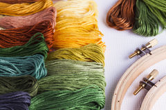 Embroidery yarns and hoops on fabric background Stock Image