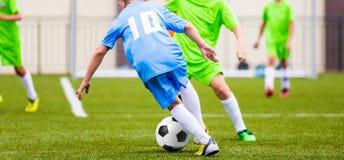 Embroma el partido de fútbol Muchachos que golpean la bola del fútbol con el pie en campo de deportes Foto de archivo libre de regalías