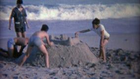 1952: Embroma la construcción de un castillo grande de la arena en la playa Miami, la Florida almacen de video