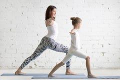 Embroma la formación del profesorado de la yoga con una posición de Virabhadrasana de la niña Imagenes de archivo