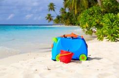 Embroma la maleta, los juguetes y el equipo del tubo respirador en la playa Imagen de archivo