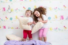 Embroma a las hermanas que juegan por las almohadas Imágenes de archivo libres de regalías