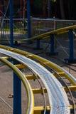 Embroma los carriles amarillos de la montaña rusa en parque de atracciones Fotos de archivo