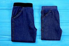 Embroma los pantalones de la mezclilla en fondo de madera fotografía de archivo