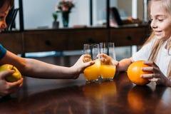 Embroma los vidrios que tintinean con el zumo de naranja Foto de archivo