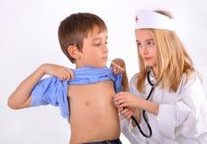 Embroma un muchacho y a una muchacha que juegan al doctor Imagen de archivo libre de regalías