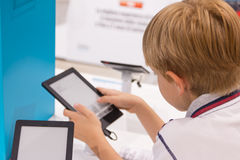 Embrome (7-8 años) jugar con la tableta en una tienda Foto de archivo libre de regalías